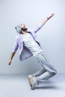 Giovane uomo alla moda bello nel ballare delle cuffie