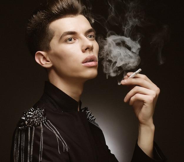 Giovane uomo alla moda che fuma una sigaretta