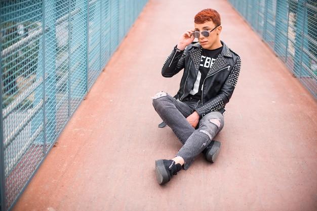Giovane uomo alla moda che si siede su un ponte