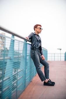 Giovane uomo alla moda che sta su un ponte