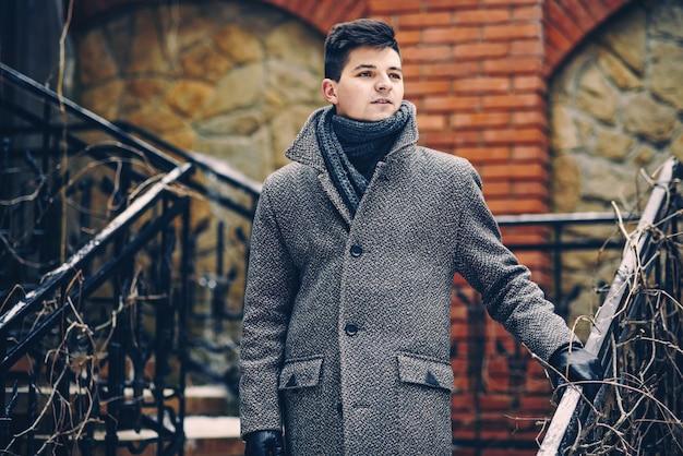 Giovane uomo alla moda in caldo cappotto grigio e guanti di pelle che cammina giù per le scale