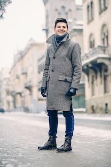 Giovane uomo alla moda in caldo cappotto grigio e guanti di pelle che cammina per strada