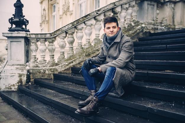 Giovane uomo alla moda in caldo cappotto grigio e guanti di pelle seduto sulle scale