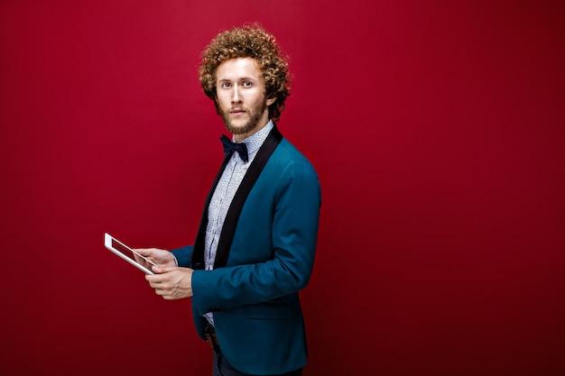 Giovane uomo alla moda in tuta con tablet