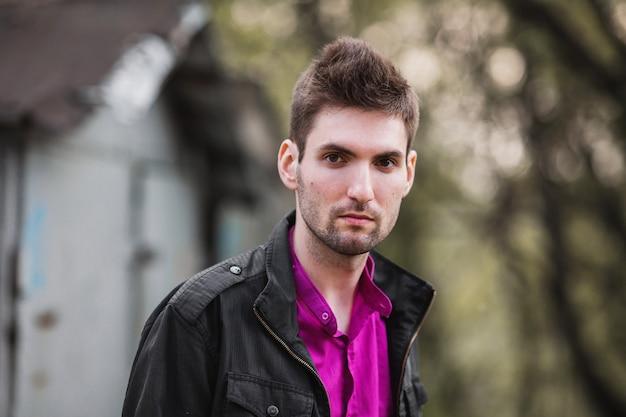 Giovane uomo allegro attraente con i capelli scuri con la barba che indossa una camicia e una giacca nera sulla strada. street style maschile. la natura in primavera. passeggiando per la città.
