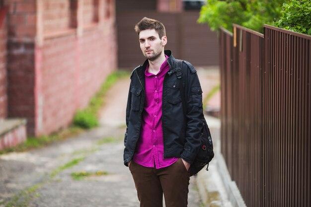Giovane uomo allegro attraente con i capelli scuri con la barba che indossa una camicia e una giacca nera sulla strada.
