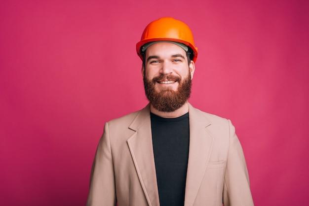 Giovane uomo allegro dell'architetto che controlla backgorund rosa e che esamina la macchina fotografica
