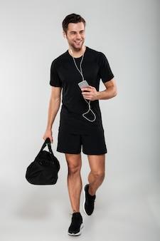 Giovane uomo allegro di sport che usando musica d'ascolto del telefono cellulare