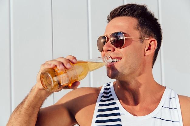 Giovane uomo allegro in occhiali da sole bere birra, mentre in piedi vicino al muro