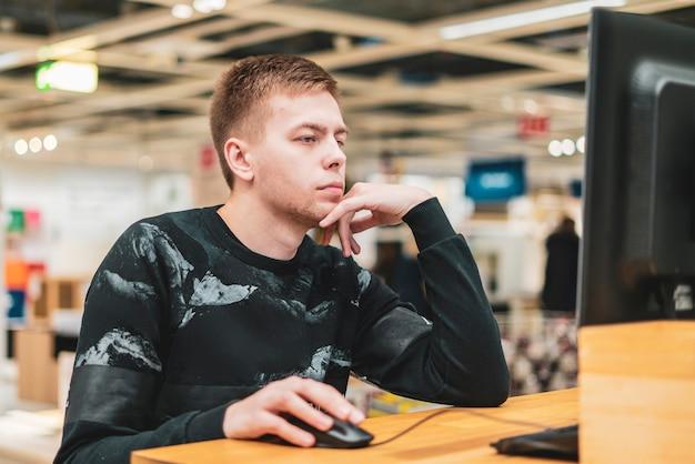 Giovane uomo ambizioso nel lavoro occasionale su un computer in ufficio