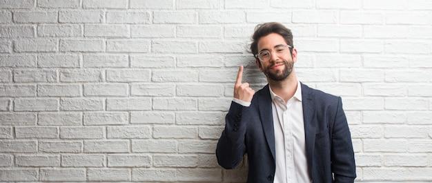 Giovane uomo amichevole di affari che mostra numero uno, simbolo di conteggio