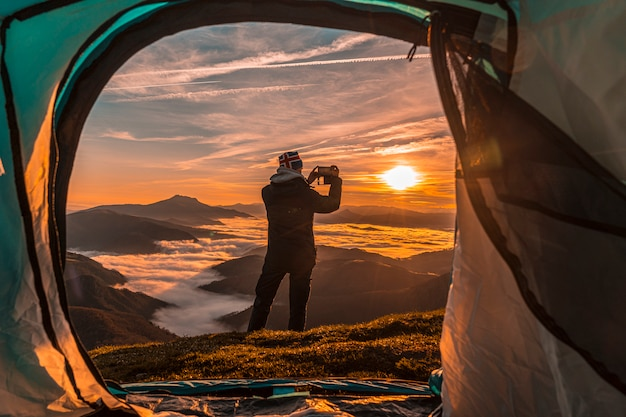 Giovane uomo appena salito dalla tenda per scattare una foto. paesi baschi