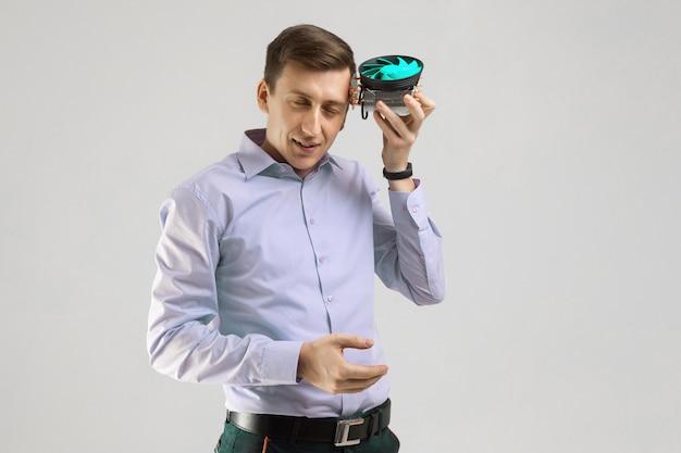 Giovane uomo appoggiato alla testa del dispositivo di raffreddamento dal computer isolato su uno sfondo chiaro