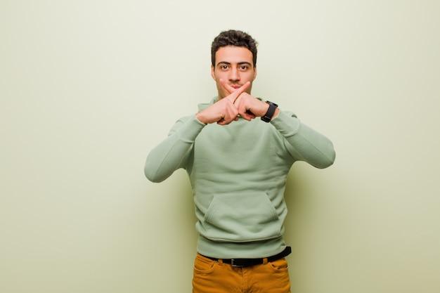 Giovane uomo arabo che sembra serio e scontento con entrambe le dita incrociate davanti in segno di rifiuto, chiedendo silenzio su una parete piatta