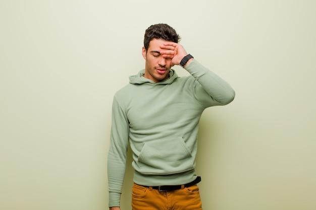 Giovane uomo arabo che sembra stressato, stanco e frustrato, asciuga il sudore dalla fronte, si sente senza speranza ed esausto contro la parete piatta