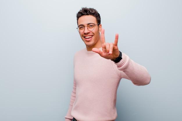 Giovane uomo arabo che si sente felice, divertente, fiducioso, positivo e ribelle, facendo segno rock o heavy metal con la mano contro il muro grigio