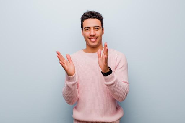 Giovane uomo arabo che si sente felice e di successo, sorridente e battendo le mani, dicendo congratulazioni con un applauso sul muro grigio