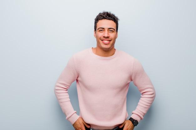 Giovane uomo arabo che sorride allegramente e casualmente con un'espressione positiva, felice, sicura e rilassata sul muro grigio