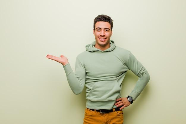 Giovane uomo arabo che sorride, sentendosi sicuro, di successo e felice, mostrando il concetto o l'idea sullo spazio della copia sul lato sulla parete piana