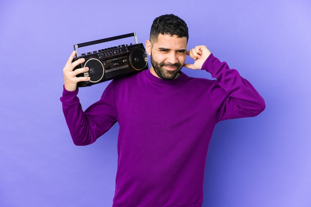 Giovane uomo arabo che tiene una cassetta radio isolata musica d'ascolto del giovane uomo arabo che copre le orecchie con le mani.