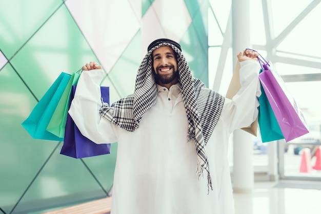 Giovane uomo arabo con pacchetti in piedi nel centro commerciale