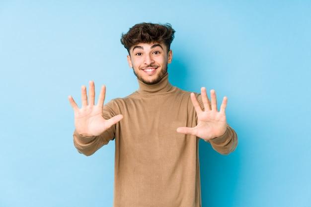 Giovane uomo arabo isolato che mostra il numero dieci con le mani.