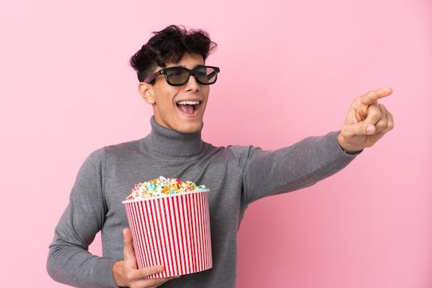 Giovane uomo argentino sopra la parete bianca isolata con gli occhiali 3d e tenendo un grande secchio di popcorn mentre punta lontano