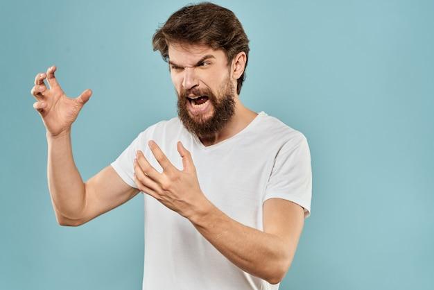 Giovane uomo arrabbiato con la barba in maglietta bianca