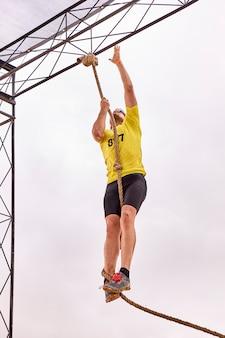 Giovane uomo arrampicata su una corda di nodi in una gara spartana