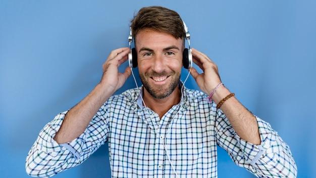 Giovane uomo ascoltare musica con gli auricolari