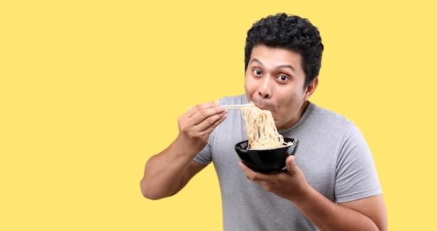 Giovane uomo asiatico alla moda bello che mangia noodle istantanei caldi e piccanti yummy usando le bacchette e la ciotola