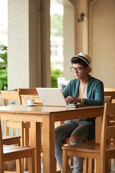 Giovane uomo asiatico alla moda che si siede alla tavola in caffè e che lavora al computer portatile