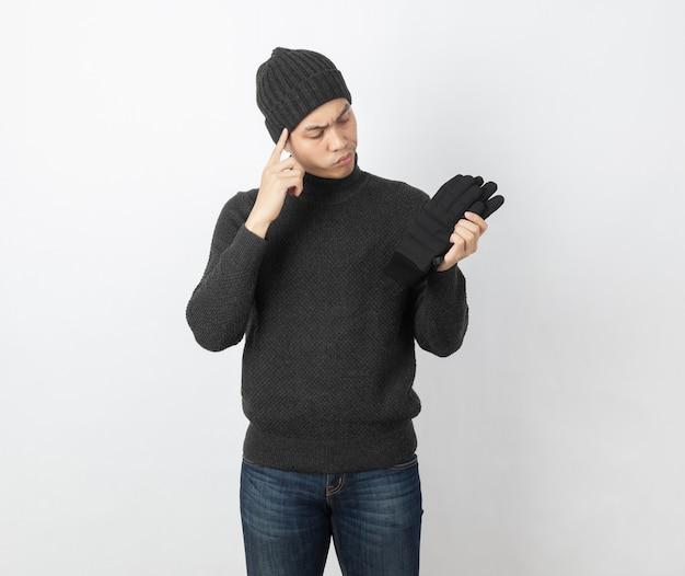 Giovane uomo asiatico bello che indossa maglione grigio e berretto che guardano ai suoi guanti caldi