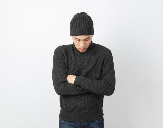 Giovane uomo asiatico bello che indossa maglione grigio e berretto che si abbraccia e tremante, tremante dal vento freddo, congelamento