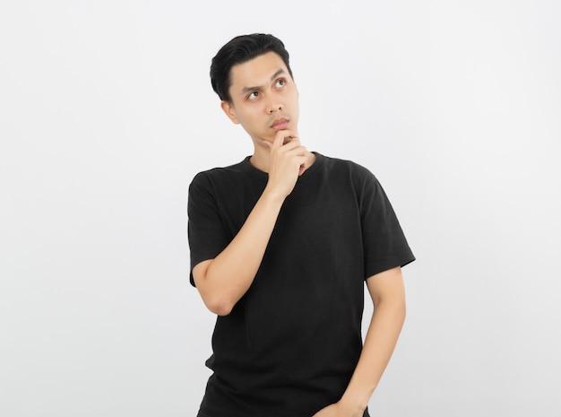 Giovane uomo asiatico bello che pensa un'idea mentre osservando in su isolato su bianco