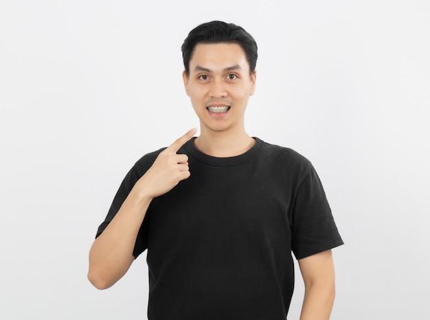 Giovane uomo asiatico bello che sorride con le parentesi graffe con indicare del dito isolato su bianco
