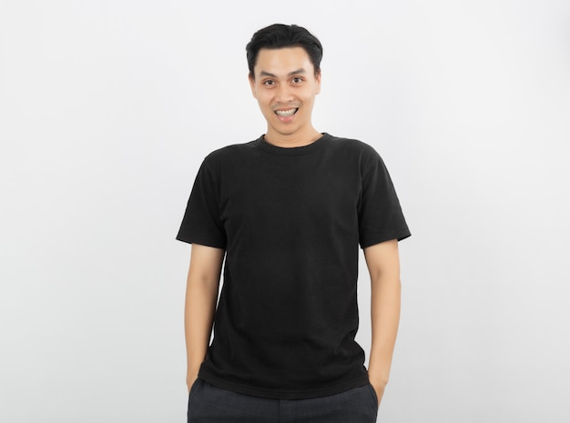 Giovane uomo asiatico bello che sorride con le parentesi graffe e che esamina macchina fotografica isolata su priorità bassa bianca.