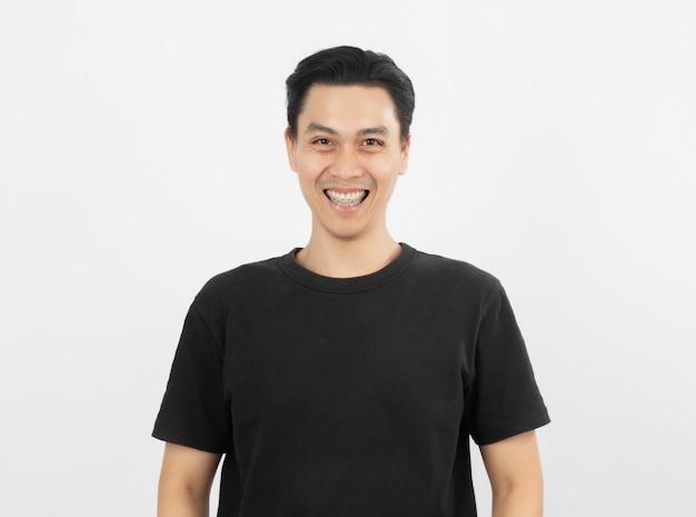Giovane uomo asiatico bello che sorride con le parentesi graffe e che esamina macchina fotografica
