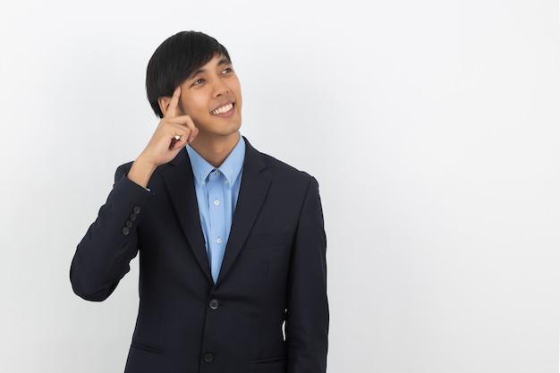 Giovane uomo asiatico bello di affari che pensa un'idea mentre cercando isolato su bianco