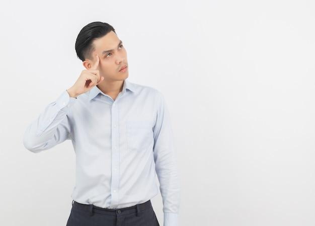 Giovane uomo asiatico bello di affari che pensa un'idea mentre osservando in su isolato su bianco