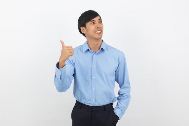 Giovane uomo asiatico bello di affari che sorride e che mostra i pollici in su isolati su bianco