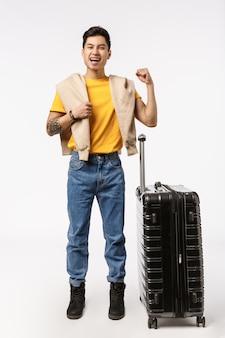 Giovane uomo asiatico bello in maglietta gialla pronta a viaggiare con la borsa del carrello