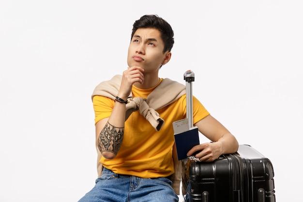 Giovane uomo asiatico bello in maglietta gialla pronta a viaggiare con la borsa e il passaporto del carrello
