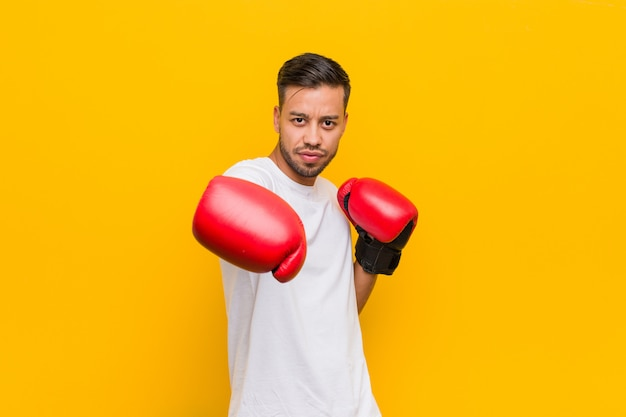 Giovane uomo asiatico boxe su giallo