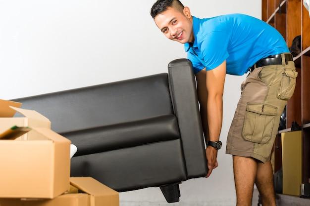Giovane uomo asiatico che alza un divano