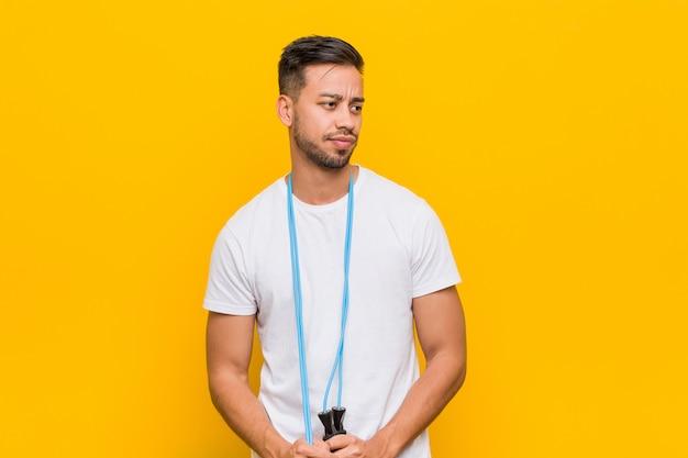 Giovane uomo asiatico che fa esercizio contro il giallo