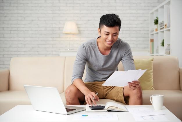 Giovane uomo asiatico che lavora a casa
