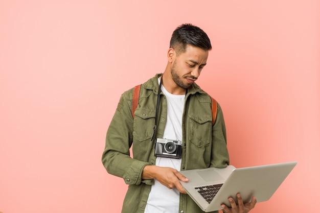 Giovane uomo asiatico che lavora sul suo computer portatile