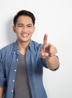 Giovane uomo asiatico che preme bottone invincibile, isolato