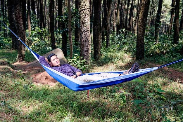 Giovane uomo asiatico che si distende sull'amaca che appende fra gli alberi